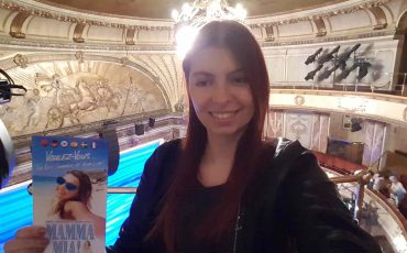 A photo of me holding a leaflet advertising Mamma Mia, standing in the theater where it played