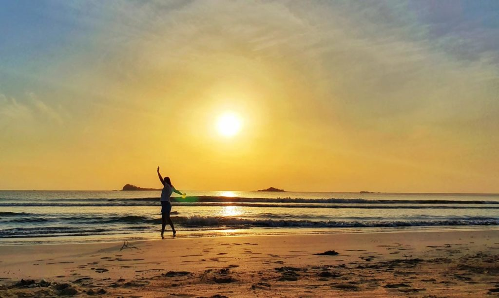 Sunrise on the beach: the sky ir orange, with the sun raising from below the water. The sand and the sea have a golden color because of the sunrise. A person is dancing on the beach, in front of the sun.
